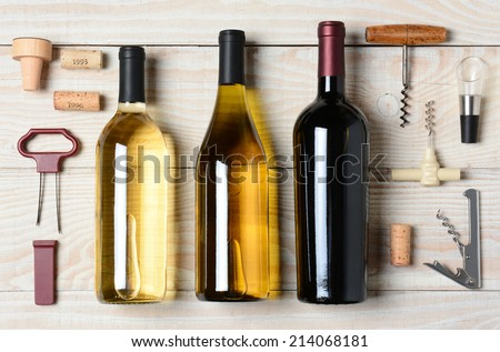 High angle shot of three wine bottles surrounded by accessories such as corkscrews, stoppers, pourers and corks. Horizontal format on a rustic white wood table. - stock photo