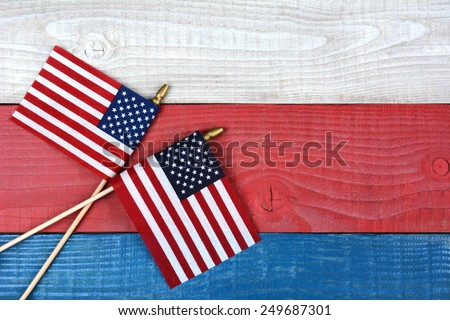 High angle shot of two crossed American flags on a red, white and blue picnic table. Horizontal format with copy space. - stock photo