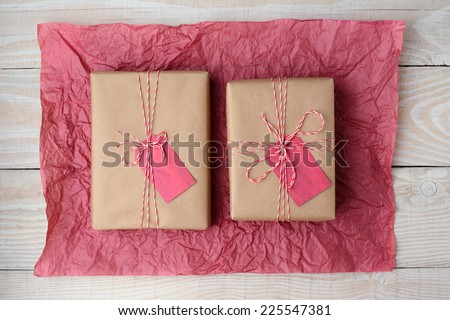 High angle shot of two plain brown paper wrapped presents on a crumpled sheet of red tissue paper. Horizontal format on a rustic white wood table. - stock photo