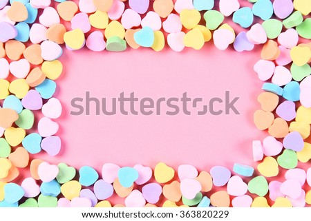 High angle shot of Valentines Day candy hearts on a pink background with copy space. The hearts form a frame around the pink background. - stock photo