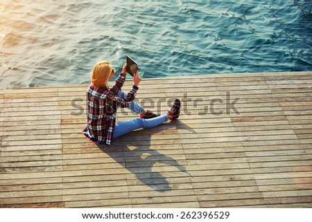 High angle shot of young tourist woman taking a photo of a beautiful view with her camera tablet, cute hipster girl relaxing at her sunny holiday photographing outdoors, young woman on sea pier, flare - stock photo