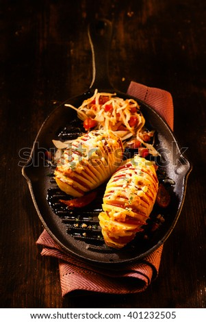 High Angle Still Life of Sliced Baked Potatoes Garnished with Sliced Salami Meat and Melted Cheese Served on Hot Cast Iron Pan on Rustic Wooden Table - stock photo