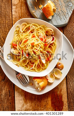 High Angle Still Life of Spaghetti Pasta with Clams Served in White Dish with Bread Roll on Rustic Wooden Table as seen from Directly Above