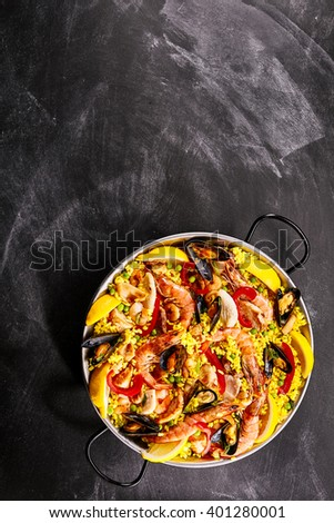High Angle Still Life View of Colorful Seafood Paella Dish with Yellow Rice Served in Pan with Handles on Smudged Chalkboard Background with Copy Space - stock photo