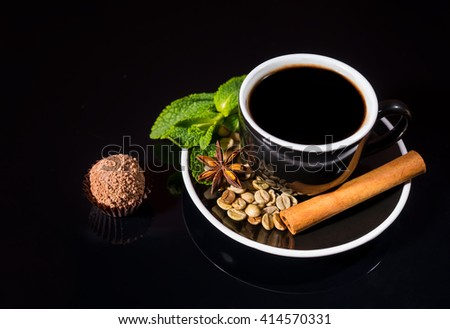 High Angle Still Life View of Cup and Saucer with Strong Black Coffee with Raw Beans, Fresh Mint and Cinnamon Stick Served with Gourmet Milk Chocolate Truffle on Shiny Black Reflective Counter - stock photo