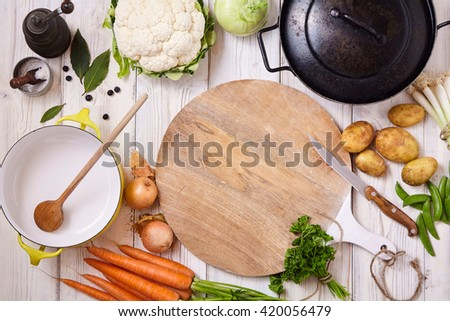 High Angle Still Life View of Cutting Board, Knife and Wok Frying Pan Surrounded by Fresh Raw Vegetables on Painted Wood Table - Preparing a Meal with Raw Ingredients - stock photo