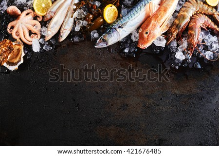 High Angle Still Life View of Variety of Raw Fish and Seafood Chilling on Ice with Lemon and Arranged Around Border of Image on Rustic Wooden Table Surface with Copy Space - stock photo