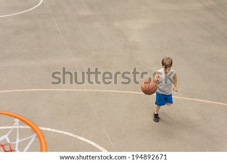High angle view from on top of the hoop of a sporty young boy playing basketball on an outdoor court running with the ball - stock photo