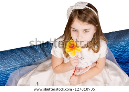 High angle view of a beautiful little girl holding a single colourful orange artificial flower to her cheek wearing a bow in her hair with copyspace - stock photo