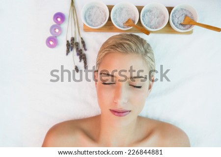 High angle view of a beautiful young woman lying on massage table at spa center - stock photo