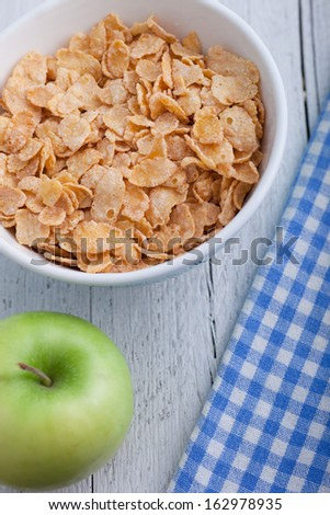 High angle view of a bowl of commercial breakfast cereal with corn flakes with a fresh green apple for a healthy meal in a rustic setting on white painted boards with a checked blue and white napkin - stock photo