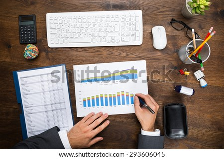 High Angle View Of A Businessman Analyzing Financial Graph On Desk - stock photo