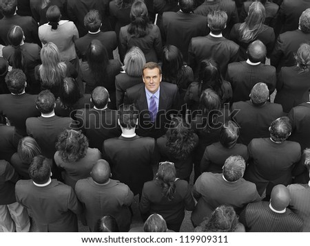 High angle view of a businessman standing amidst businesspeople - stock photo