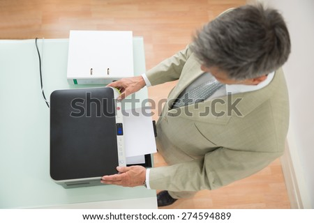 High Angle View Of A Businessman Using Photocopy Machine In Office - stock photo