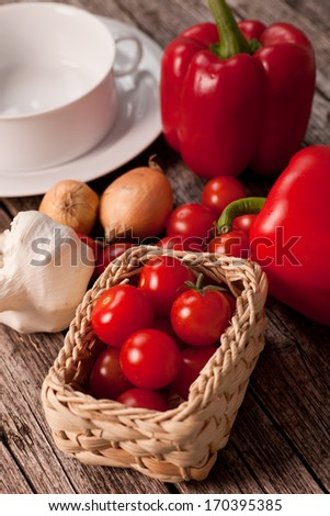 High angle view of a collection of fresh ingredients for vegetable soup including cherry tomatoes, peppers, onion and garlic alongside an empty soup bowl - stock photo