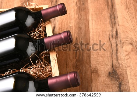 High angle view of a crate of wine bottles on a wood table with copy space. - stock photo