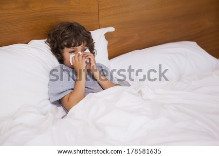 High angle view of a cute little boy suffering from cold as he lies in bed - stock photo