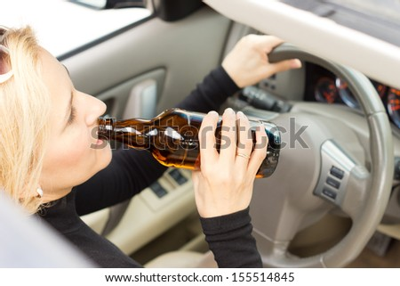 High angle view of a drunk woman driver sitting behind her steering wheel imbibing from a bottle of alcohol as she drives - stock photo