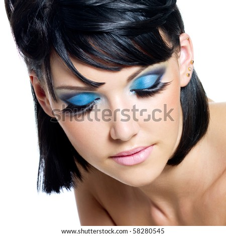 High angle view of a face of a beautiful young woman with blue make-up. Isolated on white - stock photo