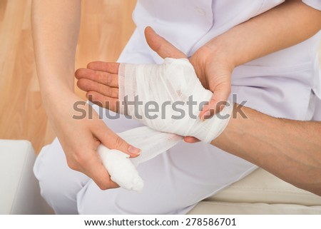 High Angle View Of A Female Doctor Bandaging Patient's Hand - stock photo