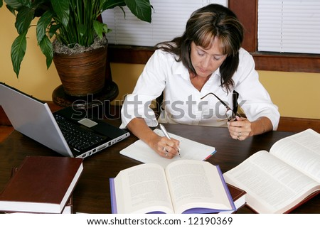 high angle view of a female researcher working in books and on the computer