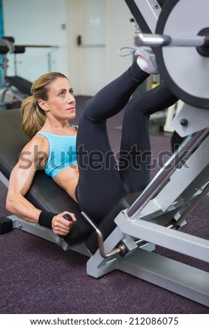 High angle view of a fit young woman doing leg presses in the gym - stock photo