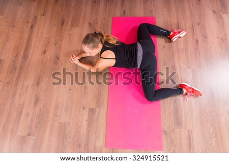 High Angle View of a Fit Young Woman Stretching her Legs While Lying on her Stomach on Top of a Fitness Mat. - stock photo