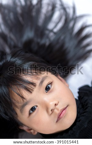 High angle view of a girl lying on back. - stock photo