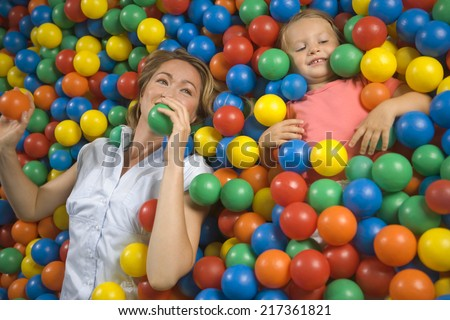 High angle view of a girl with a mid adult woman lying in a ball pool - stock photo