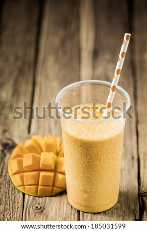 High angle view of a glass of tropical mango smoothie blended with yogurt and ice cream with fresh fruit on an old weathered wooden table with copyspace - stock photo