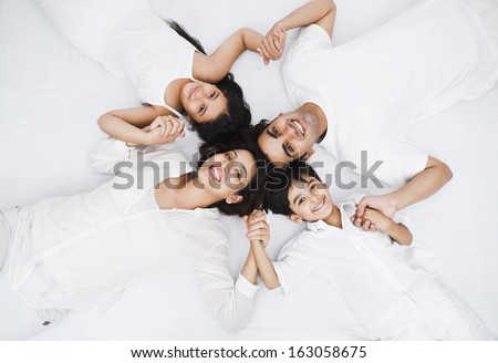 High angle view of a happy family lying on the bed - stock photo