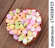 High angle view of a heart shaped box filled with Valentine's Day Candies. The box in the middle of a rustic wood background. The heart shaped candy is blank and ready for your message. - stock photo