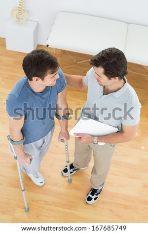 High angle view of a male therapist discussing reports with a disabled patient in the medical office