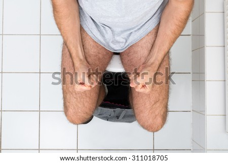 High Angle View Of A Man Clenching His Fist Sitting On Toilet Bowl - stock photo