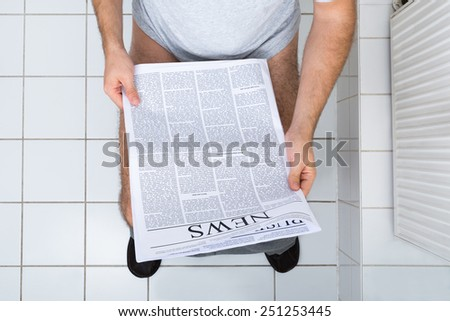 High Angle View Of A Man In Toilet Reading Newspaper - stock photo