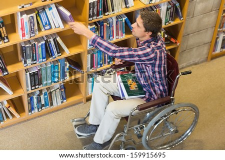 High angle view of a man in wheelchair selecting book from bookshelf in the library - stock photo
