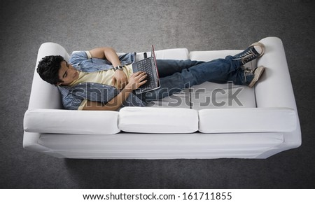 High angle view of a man lying on a couch working on a laptop
