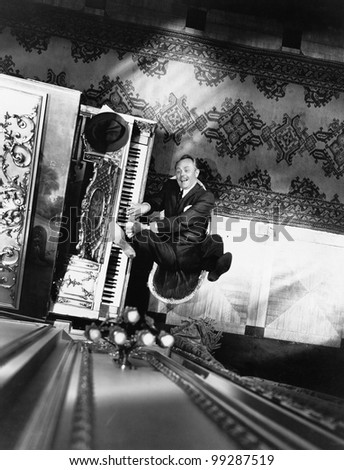 High angle view of a man reclining on a chair and playing a piano - stock photo