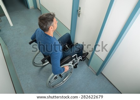High Angle View Of A Man Sitting On Wheelchair Opening Door - stock photo