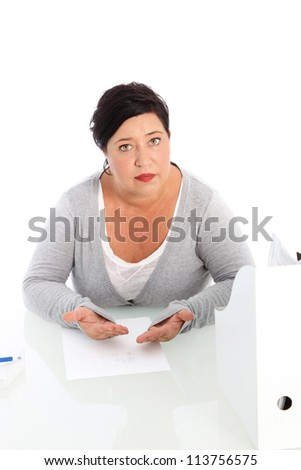High angle view of a middle-aged woman seated at a table with a sheet of paper in front of her pleading her case - stock photo