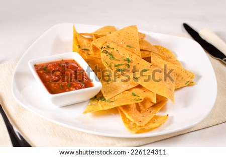 High angle view of a plate of golden spicy nachos or corn tortillas with tomato and chili salsa