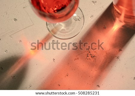 High angle view of a red wine bottle and glass with shadows and reflections on a concrete table top.