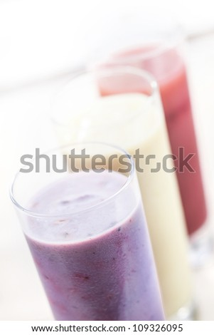 High angle view of a row of assorted fruit smoothies or milkshakes blended with healthy yoghurt in tall glasses with shallow dof - stock photo