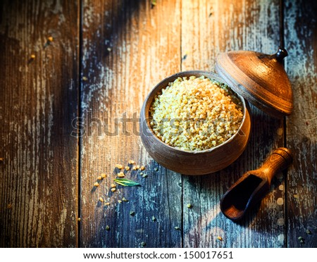High angle view of a rustic earthenware pot filled with dried bulgur, a popular Middle Eastern ingredient made from cracked or crushed durum wheat - stock photo