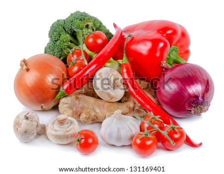 High angle view of a selection of fresh farm vegetables including, peppers, tomato, chilli, onions, mushrooms and broccoli on a white studio background - stock photo