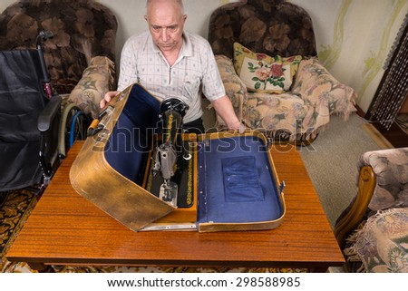 High Angle View of a Senior Tailor Man Putting his Manual Sewing Machine in a Vintage Carrying Case on Top of the Table. - stock photo