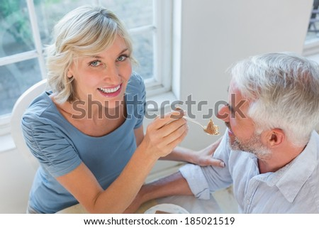 High angle view of a smiling woman feeding mature man pastry at home
