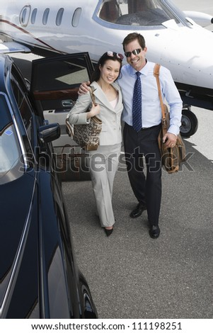 High angle view of a successful business couple standing together with arm around at airfield - stock photo