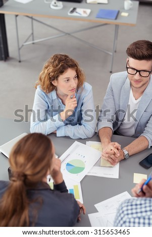 High Angle View of a Thoughtful Young Office Woman Listening to her Colleague While in a Business Meeting. - stock photo