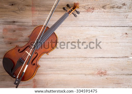 High Angle View of a Violin Musical Instrument Lying on a Wooden Floor with Copy Space on the Right Side. - stock photo